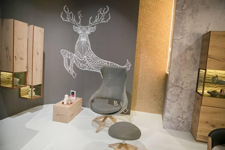 Bild eines grauen Sessels sowie beleuchteter Regale von Voglauer